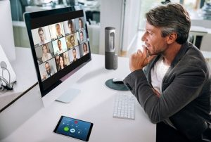 a man looking at a screen with 12 live video conference windows
